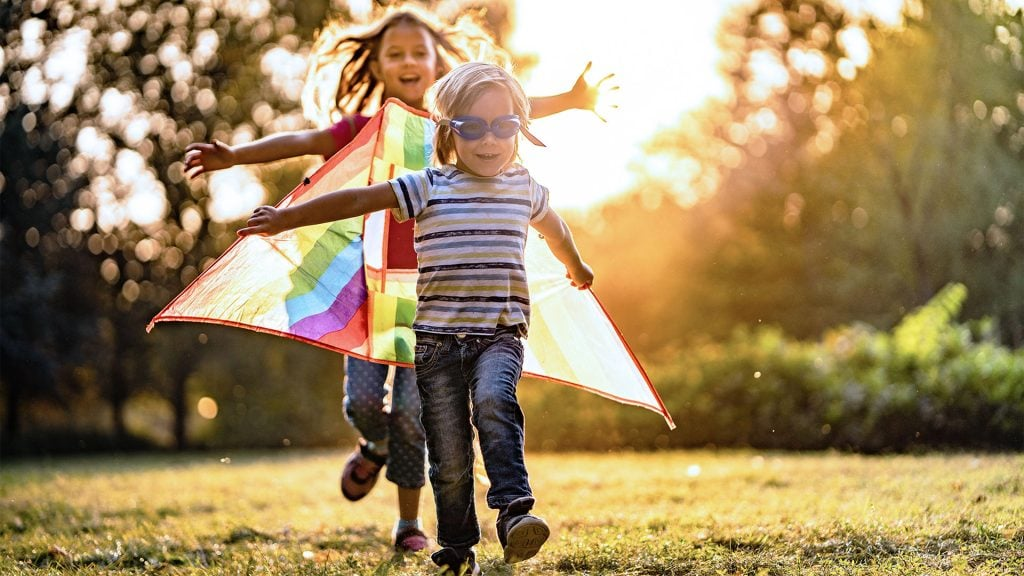 boy and girl running with a kite