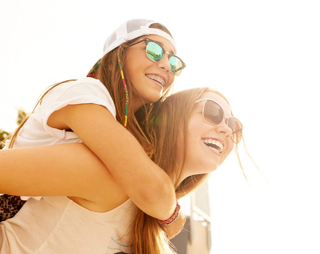 a teen girl giving another teen girl a piggyback ride smiling